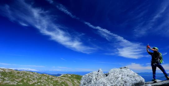 碧空の雲と登山者