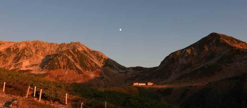 夕日に染まる立山と月