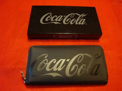 コカ・コーラさんのクレーンゲームの景品の黒い長財布の写真。ケースと共に。赤い布の上に並べて置いてあります。