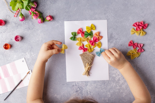 small-child-doing-bouquet-flowers-out-colored-paper-colored-pasta_109994-66.jpg