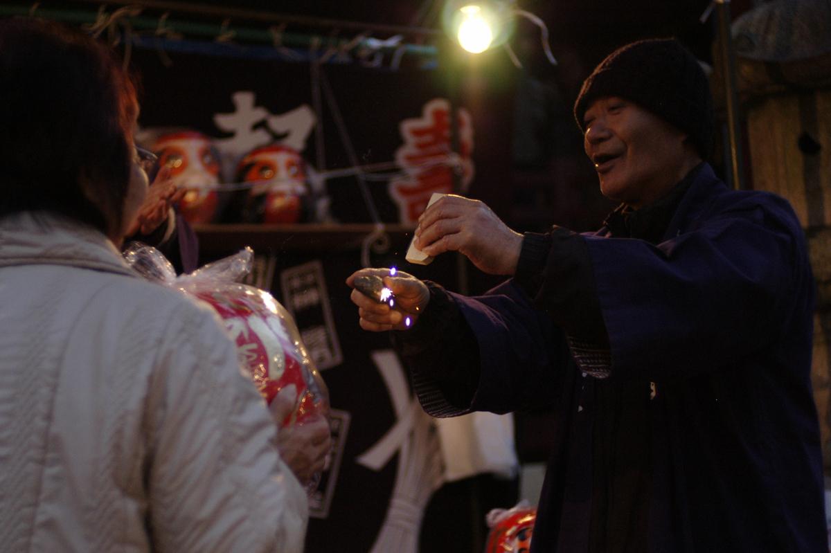 小田原スナップ飯泉観音だるま市にて火打ち石でだるまに魂を入れるだるま屋