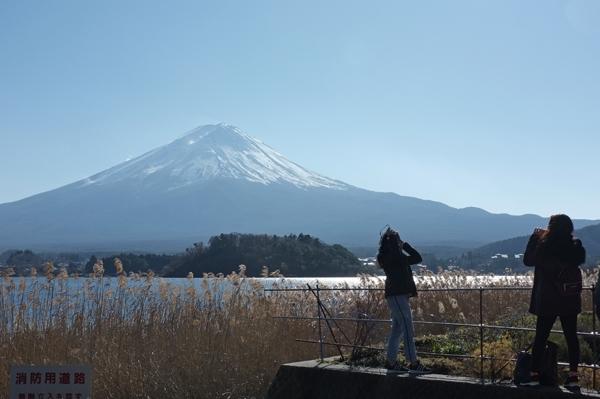 初冬の富士山の前で写真を撮る観光客