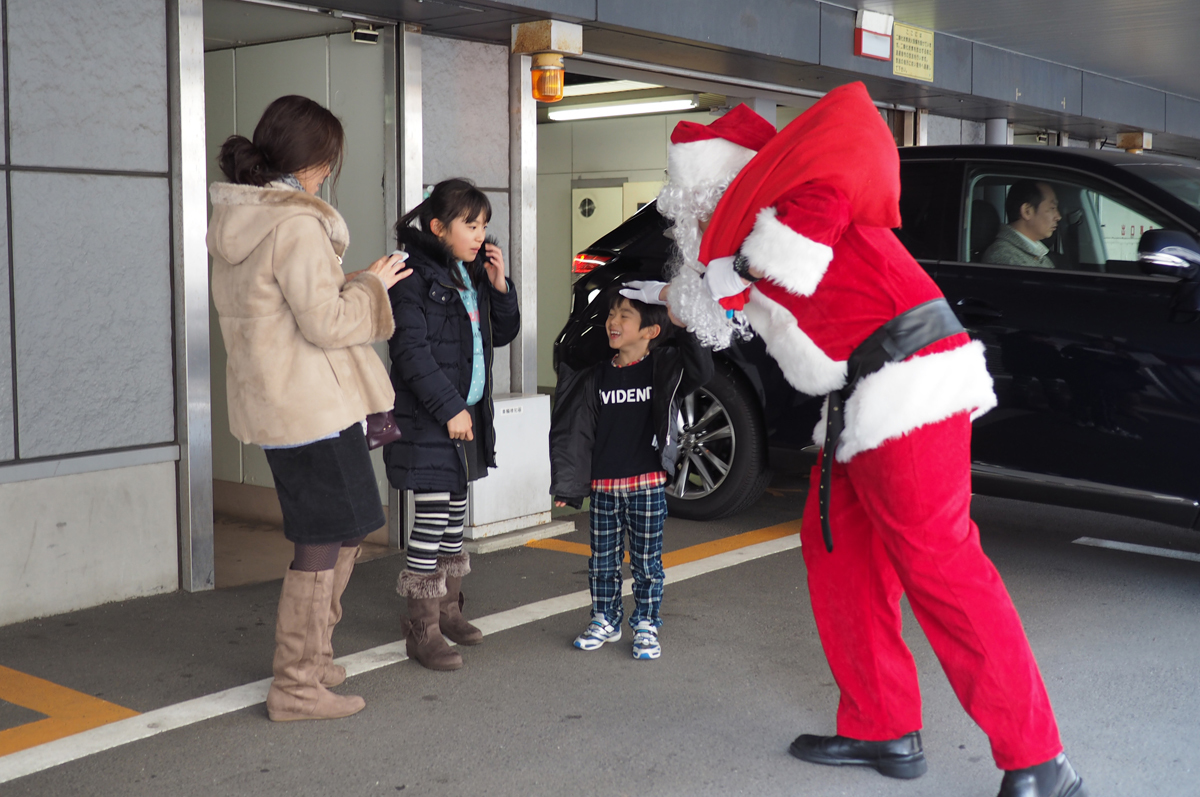 小田原スナップ街中で子供にプレゼントを手渡すサンタクロース