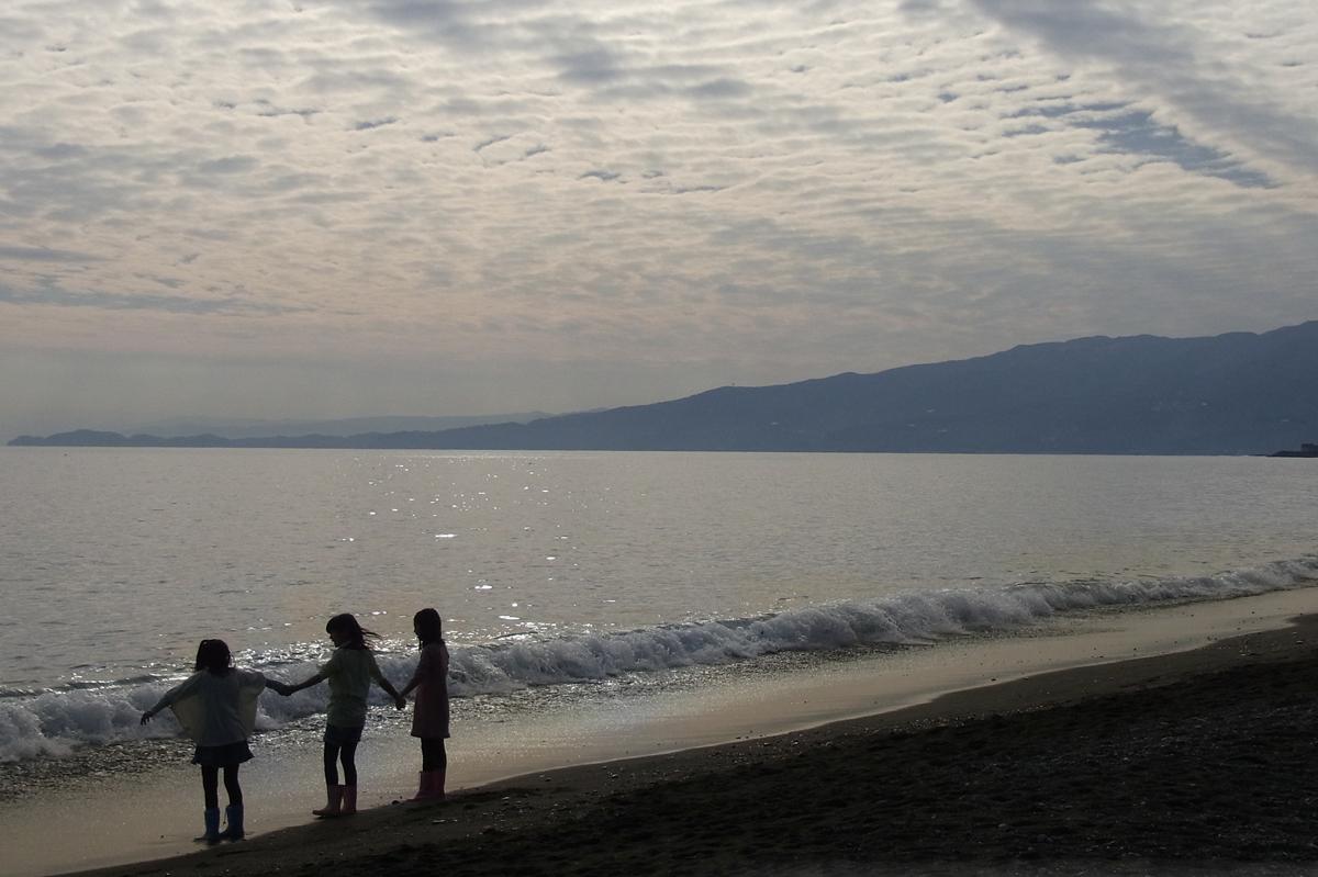 新年の海に向かって手をつなぐ子供達