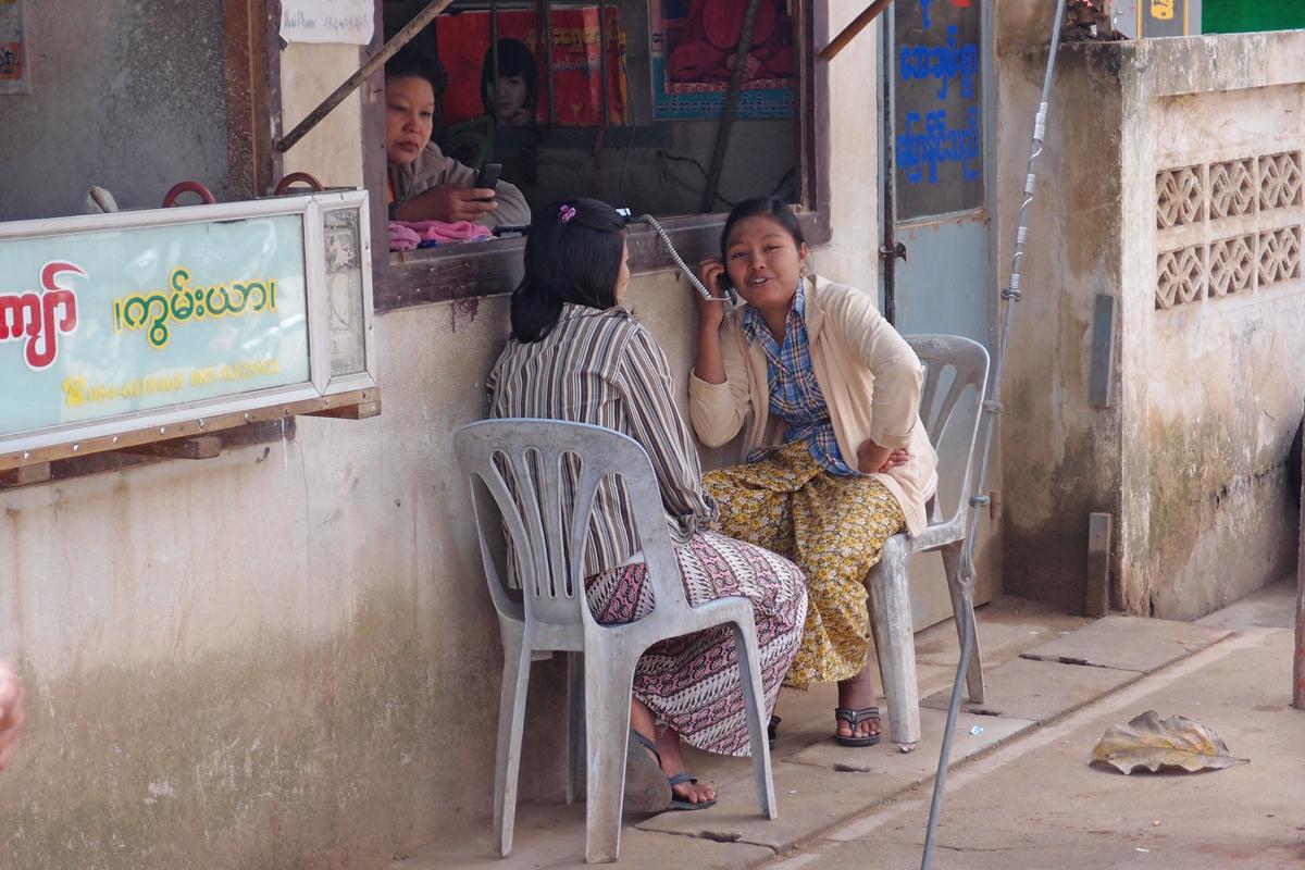 ミャンマーの街角で電話する女性