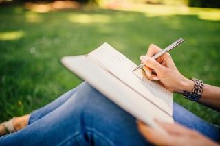 ノートにペンで筆記する人