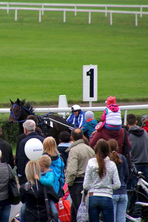 パルティニッツェ競馬場の速歩レースのゴール前 背負われる子供などの観客