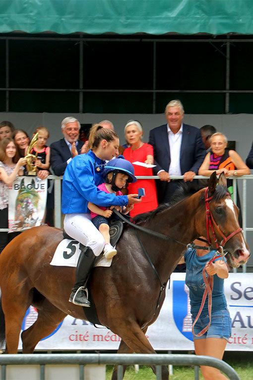 指輪祭りの表彰式 優勝した馬と馬上のママと子と指輪