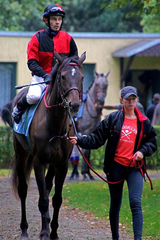 ヴロツワフ競馬場パドック 赤と黒の勝負服ジョッキーとポップロックの仔を曳く女性厩務員さん