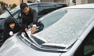 車のフロントガラスに積もった雪を払う親子=浜松市東区で